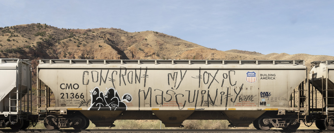 "Image of a train car in front of a barren, hilly backdrop. There is graffiti on the train car, the most prominent display is the phrase ""Confront my toxic masculinity."""