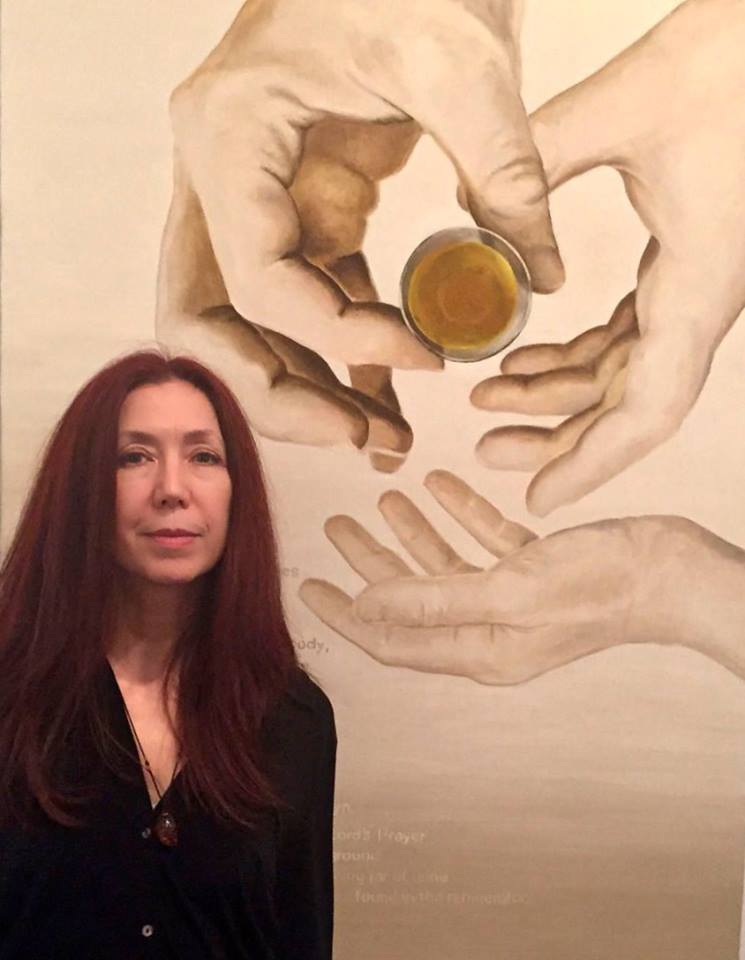 Photo of curator Linda Griggs posed in front of a painting. She is wearing a black sweater, has dark red hair past her shoulders, and is looking directly at the camera. The painting behind her is of three hands, two larger adult hands holding what looks like a small glass of brown liquid, and one smaller child-like hand. The child-like hand is open, as if ready to receive the glass from the adult's hands.