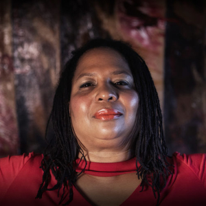 Portrait photo of Faye Victor wearing a red shirt and red lipstick. She is posing against a dark and colorful background.