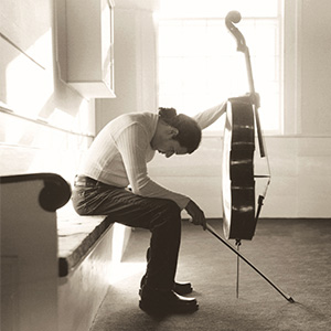 Haimovitz sitting on the left of the composition, holding a bow in one hand and instrument in the other while bent over and looking down at the ground.