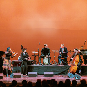 Image of the Silkroad Ensemble playing on a stage. Pictured are five musicians, left to right: a violist, a big pipe player, two drummers, and a bassist. They are playing on a stage in front of a bright orange backdrop.